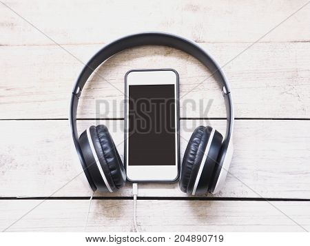 Headphone and mobile phone on white wooden background. Top view.