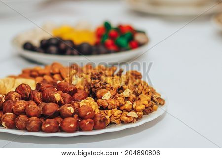 White Plate With Walnut And Filbert On Wedding Table