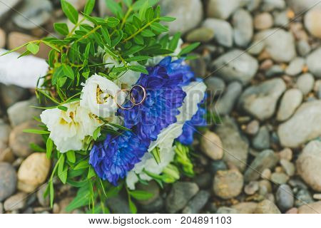 a Bridal bouquet lays on the rocks by the river