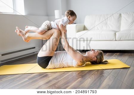A sports mother is engaged in fitness and yoga with a baby at home