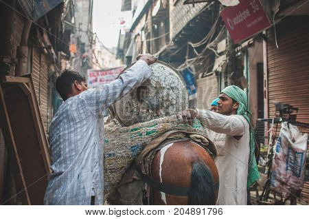 Old Delhi India : February 15th 2015 - A shot of two indian workers loading a cargo on a back of a horse in the streets of Old Delhi for delivering goods.