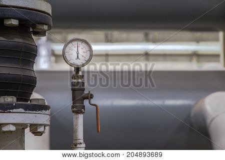 close up of industrial pipes and measurer of compressionpressure gauge