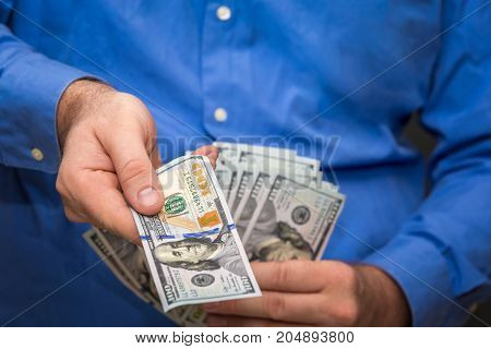 Handing over a hundred out of fanned group of hundred dollar bills