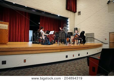 JOLIET, ILLINOIS / UNITED STATES - JULY 24, 2017: Professor Alexandra Dee conducts a rehearsal for musicians in the Saint Francis Summer Strings Music Camp, on the Sexton Auditorium stage, at the University of Saint Francis.