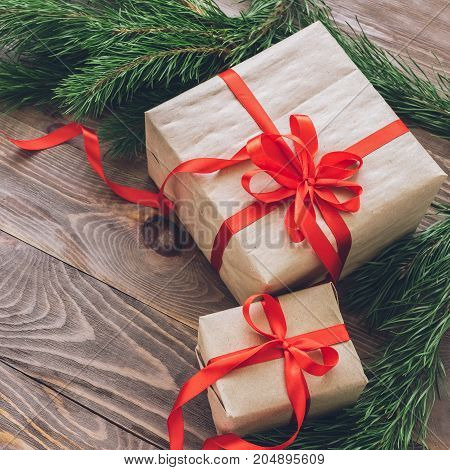 Christmas gifts in holiday boxes with red satin ribbons and fir branches on wooden background.Christmas concept. A square frame.Selective focus.