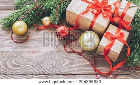 Christmas gift box with festive red satin ribbons fir branches baubles garlands Christmas decorations on wooden background. New year's concept. The horizontal frame.Selective focus.Copy space