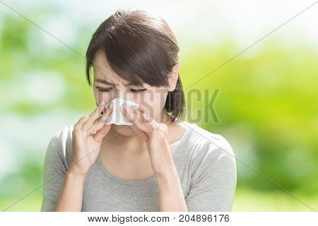 woman get sick and blow her nose on the green background