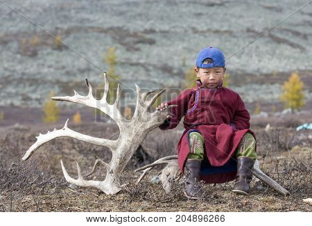tsaatan nomadic boy in a traditional deel sitting on a rein deer horn in a steppe in Northern Mongolia