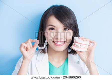 woman dentist take brace on the blue background
