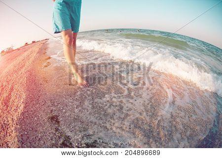 Girl Is Walking Along The Beach.