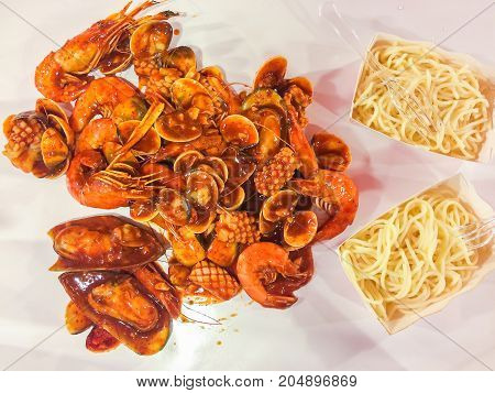 Spicy Shrimp and mixed seafood Thai Style Spicy shrimps squid shell cooked with parsley garlic with spicy sauce serve with spaghetti