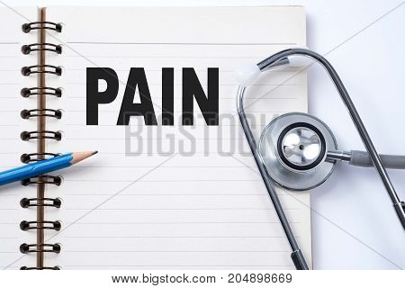 Stethoscope on notebook and pencil with PAIN words as medical concept.