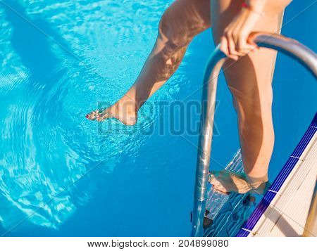 Close-up picture of sexy woman's legs in a blue pool on a colorful background. Girl with long tanned legs in a swimming pool.