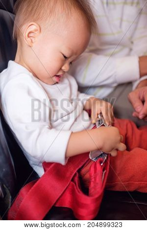Cute little Asian 20 months / 1 year old toddler baby boy child wearing & fasten red seat belts while sitting on airplane seat. Safety measures on board. Precautions on plane during flight for kid