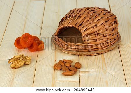 A wicker house and a treat for a hamster. Nuts dried apricots.