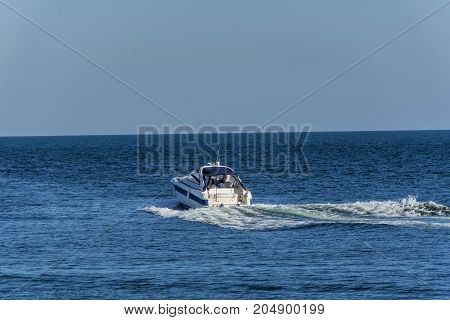 White cabin cruiser over blue water. A luxury private motor yacht under way on Black Sea sea with bow wave.