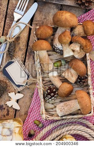 Vegetarian set: raw white mushrooms pine cones with dry decorations and decorative tag on the wooden table