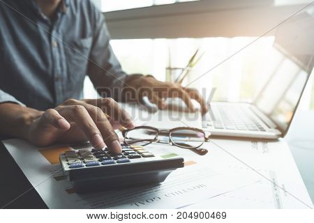 Close Up, Business Man Or Lawyer Accountant Working On Accounts Using A Calculator And Laptop Comput