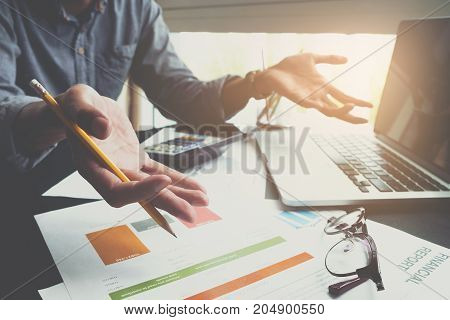 Side View Of Business Man Working At Office With Laptop And Documents On His Desk At His Office Whil