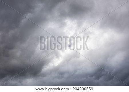 Grey Sky With Dark Clouds And Light Shining Through Them