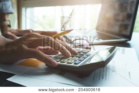 Business Man Working At Office With Calculator Laptop Computer And Documents On His Desk