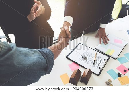 Estate Agent Shaking Hands With His Customer After Contract Signature At His Office