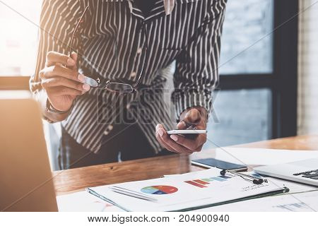 Young Businessmen Hand Holding Smartphone To Call Marketing Consultants With Their Partners To Analy