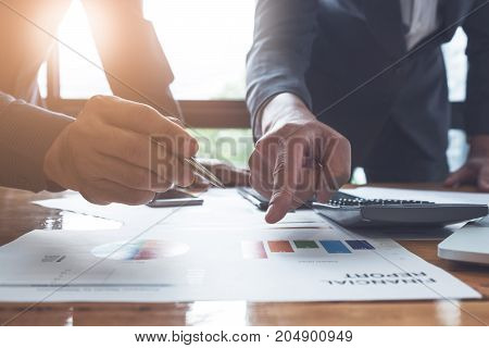 Young Business Man And Partner Pointing On Financial Report For  Analyze The Company's Sales Plan In