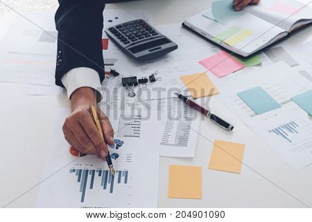 Businessman Pen Pointing Graph Chart In This Mounth And Use Calculator For Marketing Plan, Above Vie
