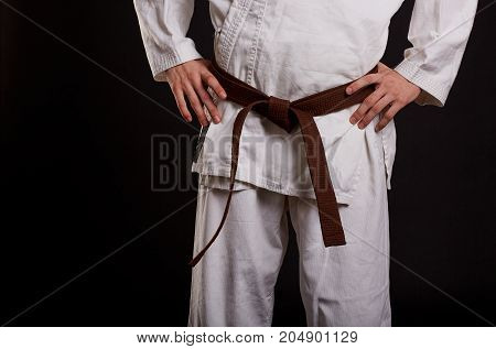 Close-up picture of a young man in a karate uniform on a black background. Fighter with a brown belt with hands on hips.