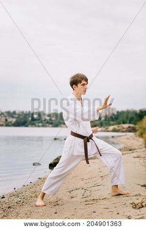 Teenage boy doing karate exercises in white kimono on a blurred nature background. Judo or taekwondo training outside. Copy space.
