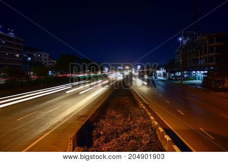 The light of the car on the road during the beautiful night time. Feel like the mood in the movie scene