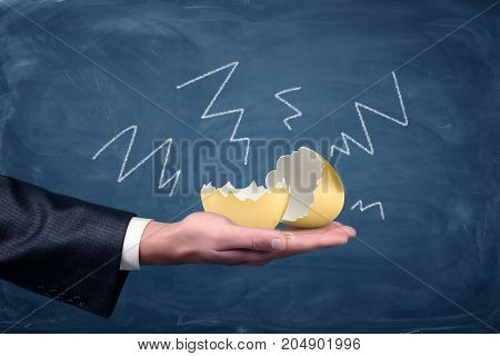 A large cracked and empty golden egg lying on a businessman's palm with negative arrows drawn on a chalkboard around it. Golden goose. Loss of money. Profit and loss.
