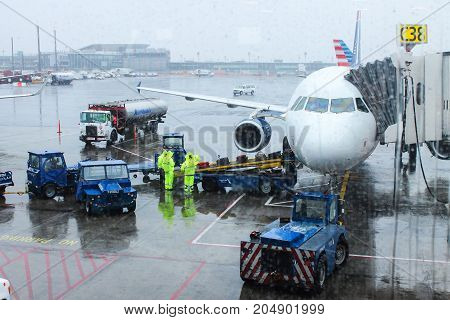 New York USA - 30 September 2016: Airport ground crew handling baggage on a rainy day at LaGuardia Airport preparing for flight.