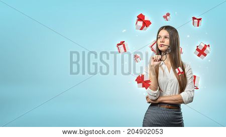 A young businesswoman stands thinking while small white and red gift boxes fly around her head. Ideas for presents. Choose client bonuses. Free gifts selection.