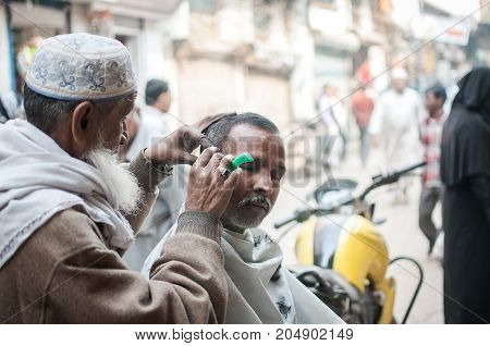 Old Delhi India : February 15th 2015 - A shot of a barber shaving out in the street of Old Delhi India.