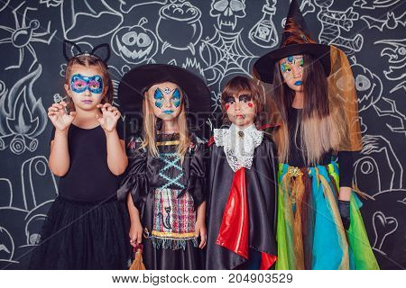 Children in scary Halloween costumes stand against a wall with drawings.