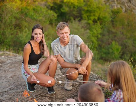 A gorgeous young romantic couple and their friends roasting marshmallows on a picnic. Smiling young travelers enjoying sunset near the campfire. Attractive girlfriend and modern boyfriend on camping.