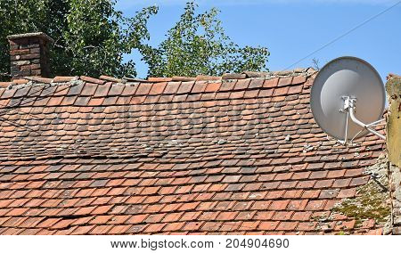 Old house roof and satellite dish in summer