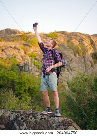 A disappointed hiking man trying to call a phone on a blurred natural background. Upset young tourist is unable to call a phone on camping in a wildlife. Bad technology and connection. Copy space.