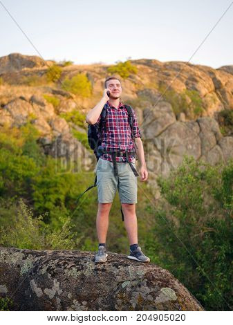 A handsome young tourist man talking on a phone standing on a rock on a blurred natural background. Healthy, active, outgoing male with a backpack hiking and relaxing in wildlife. Copy space.