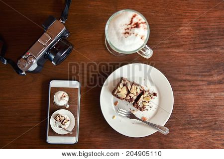 View from above. Coffee in white cup and cell phone with croissant cake marshmallows on the wooden background