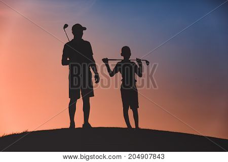 silhouettes of man with his son golfers standing with clubs on golf course at sunset