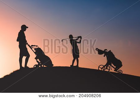 silhouettes of man with his son golfers playing golf on golf course at sunset