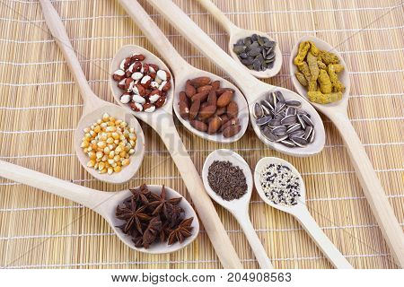 Wooden spoons group on bamboo mat with healthy seeds nuts and spices