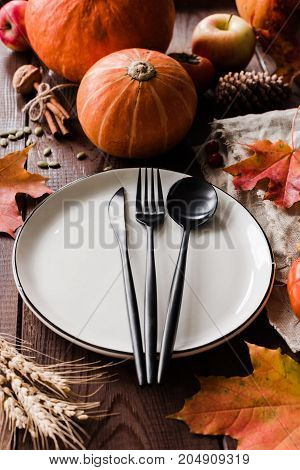 Thanksgiving dinner table setting with pumpkins, wheat, fallen leaf and black cutlery. Vertical composition, selective focus