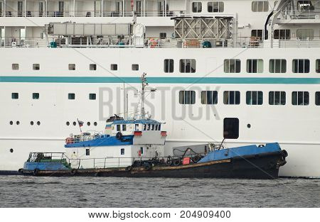 A small boat next to the cruise ship .The vehicle is refilled with fuel .