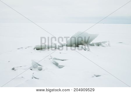 A large block of ice on the shore.White ice is very large.