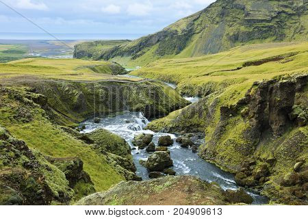 Stunning landscape with mountains and a river flowing into the waterfall Skogarfoss in Iceland