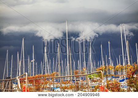 yacht mast in the port on a cloudy sky background before storm